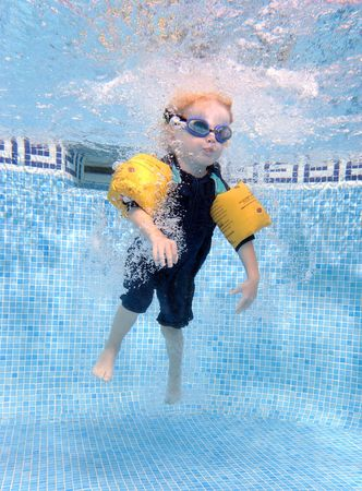 Chico joven saltando en una piscina como se ve desde bajo el agua.  Foto de archivo - 2230578