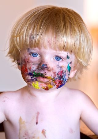 messy paint: Young happy smiling boy with face covered in colourful paint