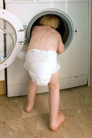 clamber: Bambino in nappy arrampicata all'interno di un bianco lavatrice