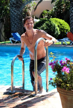 40 something: Handsome middle aged man climbing out of sunny swimming pool on vacation