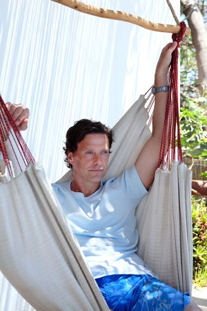 forty something: Handsome smiling middle aged man sitting in hammock on a sunny day Stock Photo