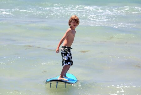 elated: Healthy young boy learning to surf in the sea or ocean