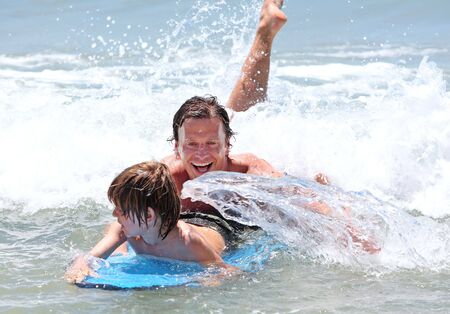 Young father and son happily learning to surf whilst on vacation in sunny Spain Stock Photo