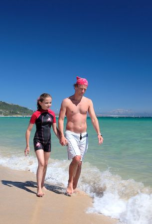 Young father and daughter walking along sunny, sandy beach on vacation or holiday holding hands photo
