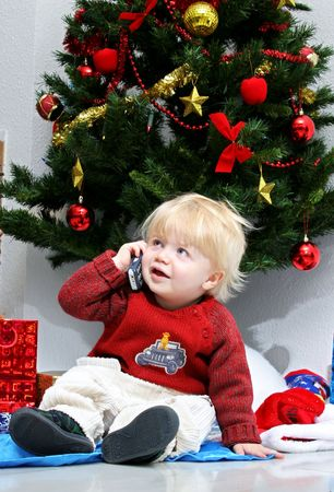 Young boy or toddler talking to Santa or Father Christmas on mobile phone under a christmas tree in big red sweater or jumper with presents all around photo
