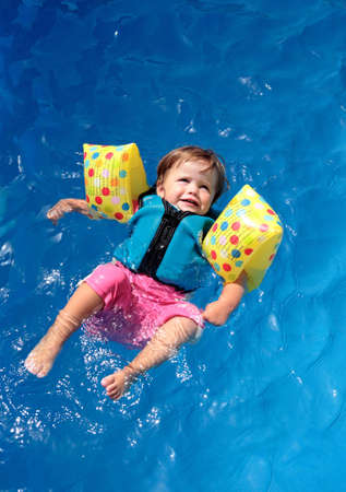 flotation:  girl floating on top of swimming pool in flotation jacket and arm bands