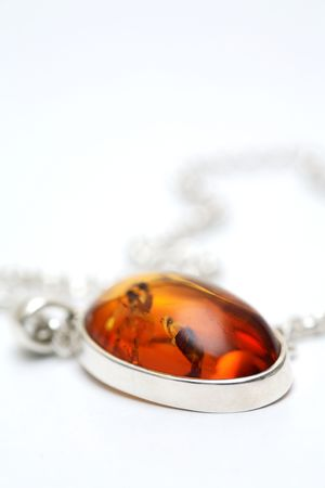 Silver necklace jewellery with Amber inlay against a white, isolated background photo
