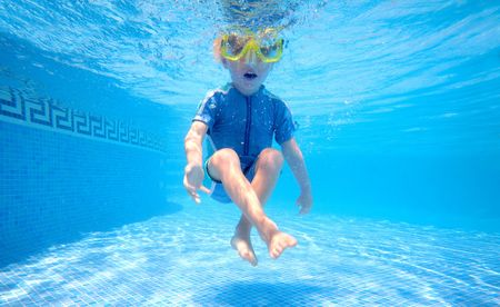 flotation: Young boy holding breath underwater in sunny swimming pool on vacation Stock Photo