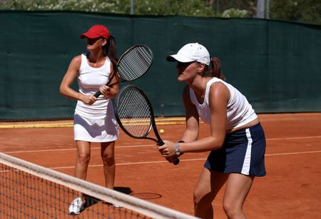 Two fit, young, tanned and healthy women playing doubles at tennis in the sun on a red asphalt court on vacation