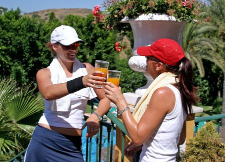 Two young, attractive, fit, tanned and healthy women drinking and toasting each other with orange juice after a hot game of tennis in the sun on vacation. Stock Photo - 2240617