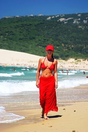 Attractive, fit young girl in red sarong, bikini and baseball cap walking along crowded white sandy sunny beach in Spain on vacation. photo