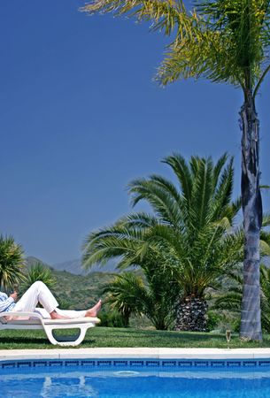 sunbed: Young man lying on a sunbed sunbathing and holding a glass of Champagne next to a luxury swimming pool