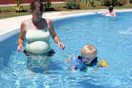 buoyancy: Chico joven en traje de flotabilidad de seguridad que se les ense�a a nadar por su madre embarazada en la piscina de vacaciones o de vacaciones