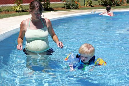 wise woman: Young boy in safety buoyancy suit being taught to swim by his pregnant mother in pool on vacation or holiday Stock Photo