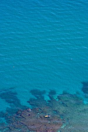 Aerial view of clear blue water and yellow boat floating over reef as seen from top of Gibraltar photo