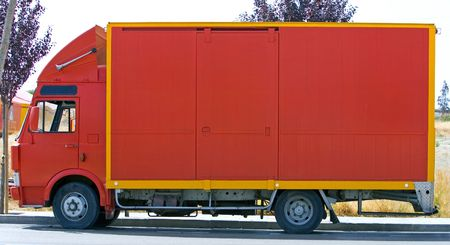 Side view of plain red lorry or van with yellow trim photo