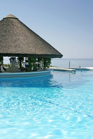 tiki bar: Tiki hut and bar by steps of swimming pool of luxury hotel on a bright sunny day in Spain