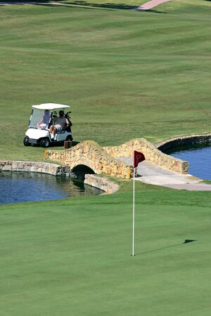 People in a golf buggy arriving at the green over a small bridge and stream photo