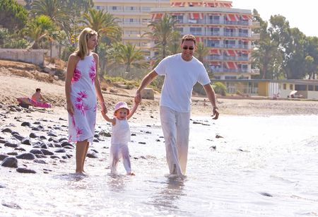 Young, healthy family walking along a sunny beach on vacation photo