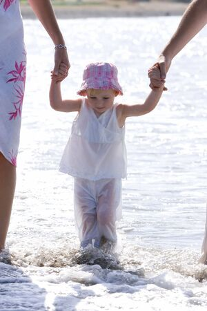 Young girl in hat being walked on beach by parents in the sun photo