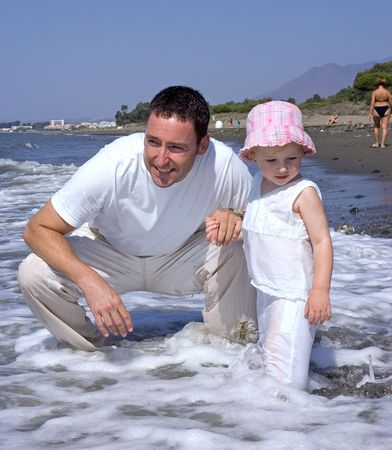 Father and young daughter playing in the sea on vacation photo