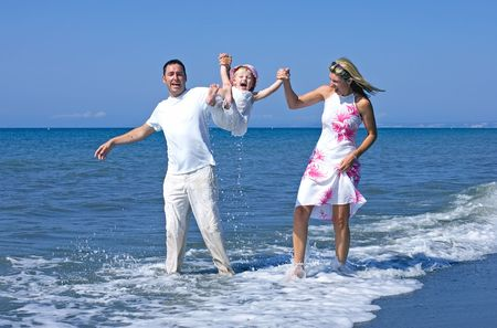 Young, happy family playing with daughter in sea on beach in Spain whilst on vacation photo