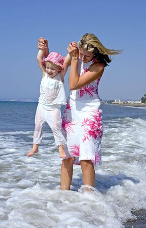 Young mother and daughter playing in the sea on a beach in Spain on vacation photo