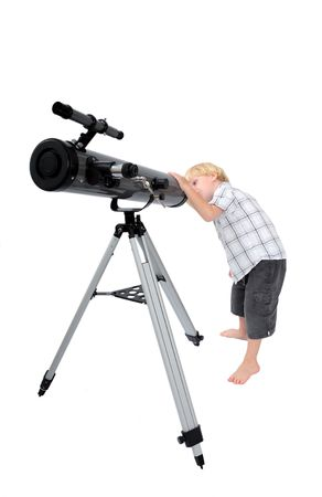 Young child or boy standing up and looking at stars through a large astrological telescope on tripod with white, isolated background
