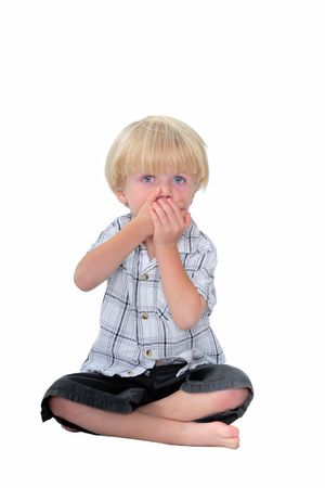 hands covering eyes: Studio photo of young boy with his hands over his mouth in surprise and white isolated background