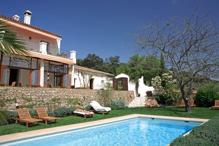 Large rustic hotel and swimming pool set in beautiful gardens in the Spanish countryside photo