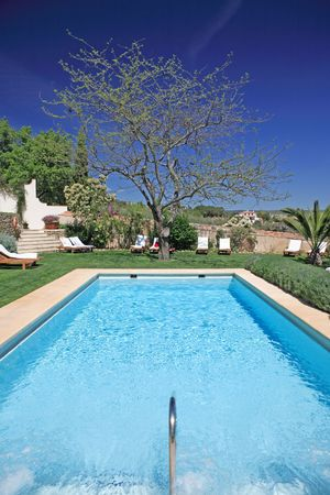 loungers: Sunny, luxurious swimming pool in rustic hotel in Spain with white sunbeds and green grass