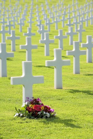 Flowers laid by cross shaped headstone of military grave