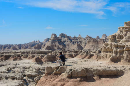 badlands: a man stand at badlands geological formations, Scenic view of the Badlands National Park Stock Photo