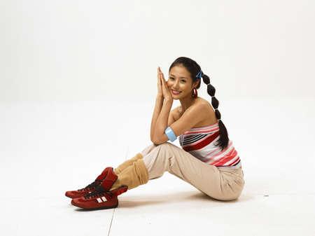 fair skin: Joven mujer sentada en el suelo, sonriendo, retrato