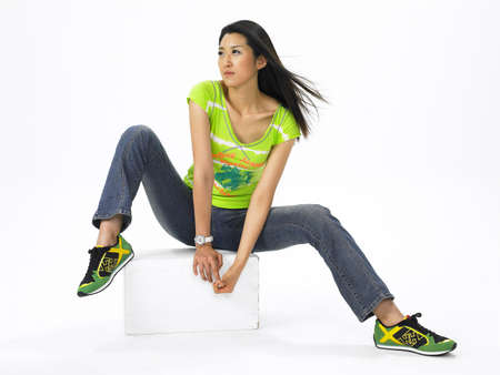 casual wear: Young woman against white background, looking away