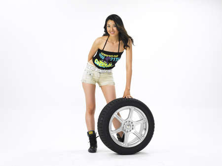 youthfulness: Portrait of a young woman standing by tire LANG_EVOIMAGES