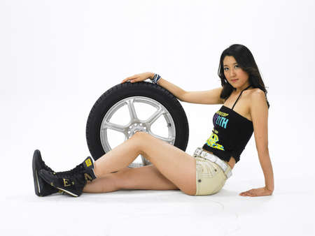 contentment: Portrait of a young woman standing by tire LANG_EVOIMAGES