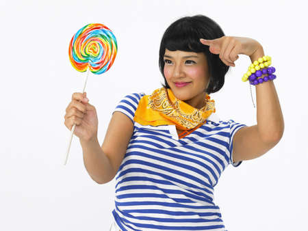 binge: Woman holding and pointing lollipop