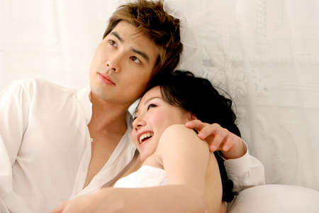 leisureliness: Young couple on bed, close up LANG_EVOIMAGES