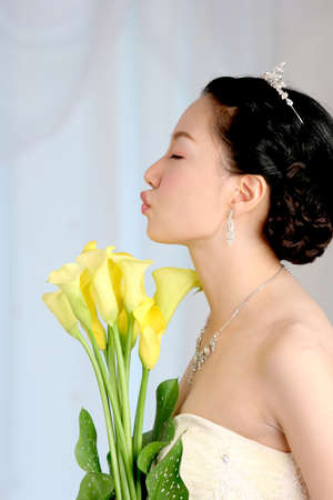 puckering lips: Bride holding flowers and puckering lips, eyes closed LANG_EVOIMAGES