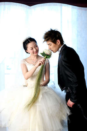 eveningwear: Young man and woman in eveningwear, man smelling flower LANG_EVOIMAGES