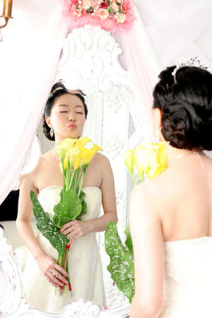 puckering lips: Bride holding flowers puckering lips in mirror, eyes closed
