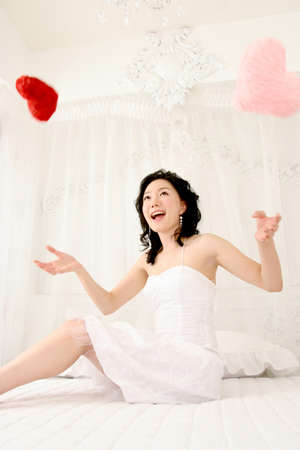 leisureliness: Young woman playing on bed