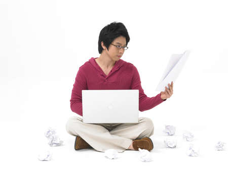 frustrate: Young man with laptop, looking at document