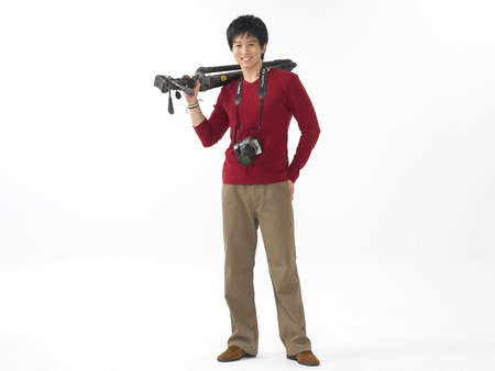cheerfulness: Portrait of a young man with digital camera and tripod