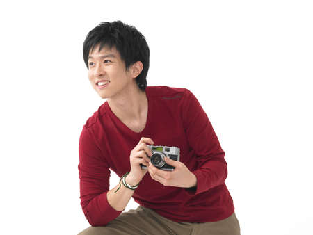 cheerfulness: Young man holding digital camera against white background LANG_EVOIMAGES