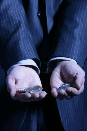 mid section: Businessman holding coins in hand, mid section LANG_EVOIMAGES
