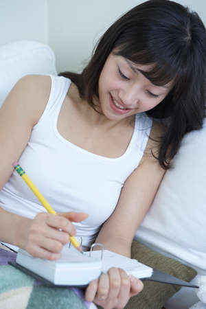 leisureliness: Young woman with book and pencil
