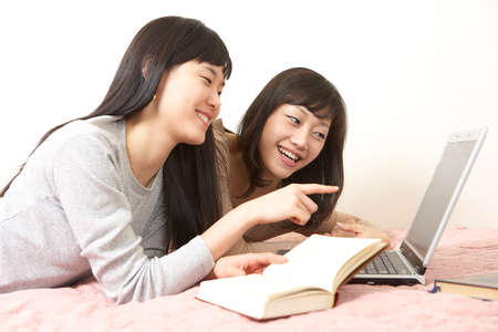 leisureliness: Two young women on bed with laptop and book, smiling LANG_EVOIMAGES