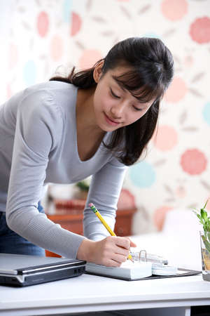 dark haired woman: Young woman writing book LANG_EVOIMAGES